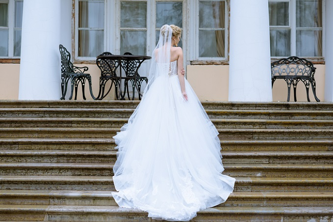 Dieses Brautkleid beweist seine Opulenz in der langen Schleppe und in der Gestaltung mit großen Rüschen bzw. Wellen im Stoff. Aus edlem Satin geschneidert, kommt das Hochzeitskleid der Garderobe einer Prinzessin aus dem Märchen gleich. (#03)